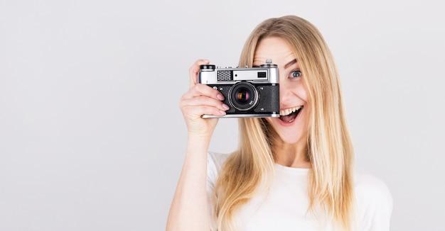 Gelukkig lachend jong meisje camera houden en het maken van foto's