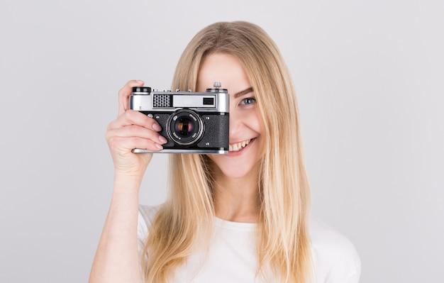 Gelukkig lachend jong meisje camera houden en het nemen van foto's