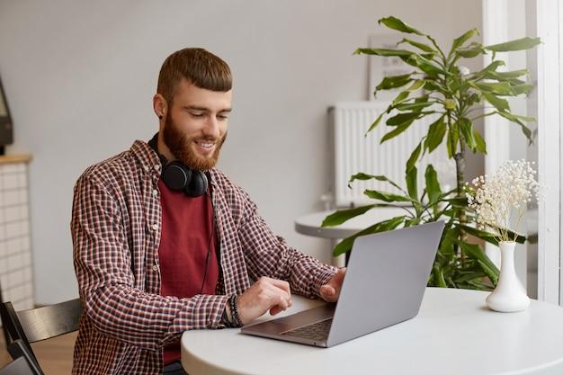 Gelukkig lachend jonge aantrekkelijke gember bebaarde man zit aan een tafel in een café en werkt op een laptop, gekleed in basiskleding.
