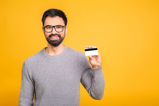 Gelukkig lachend jonge bebaarde man met creditcard geïsoleerd op gele achtergrond. Premium Foto