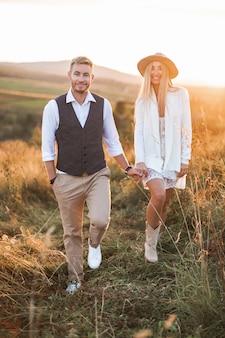 Gelukkig lachend jonge hippie cowboy stijl paar hand in hand en wandelen in de zomer veld, buitenshuis. vrouw in jurk en cowboylaarzen, man in casual pak