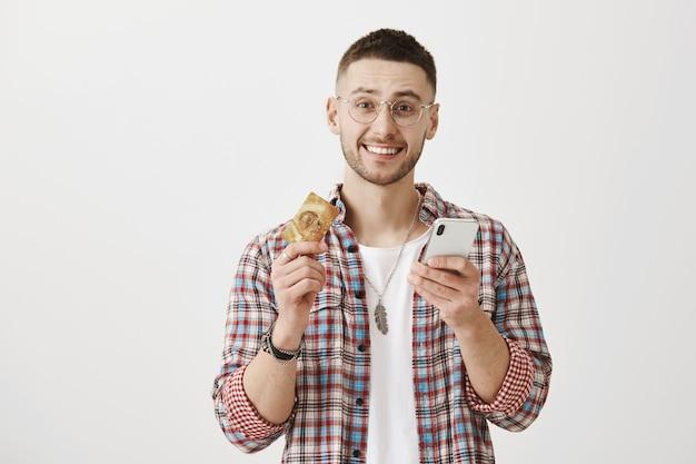 Gelukkig lachend jonge man met een bril poseren met zijn telefoon en kaart