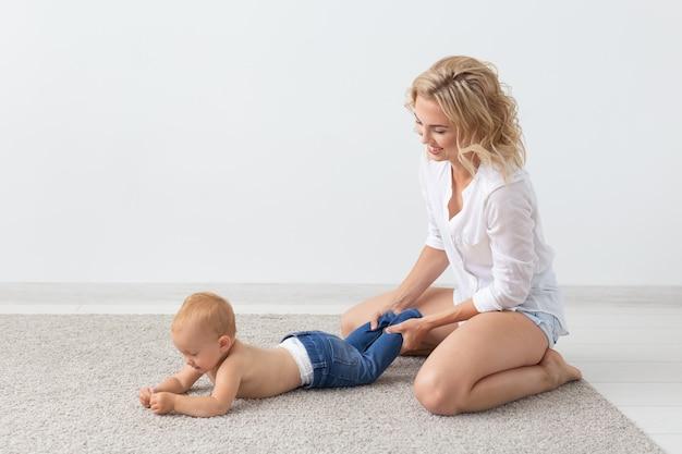 Gelukkig lachend jonge moeder spelen met kleine baby thuis