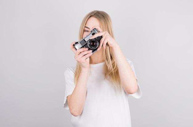 Gelukkig lachend jonge vrouw met camera en het maken van foto's
