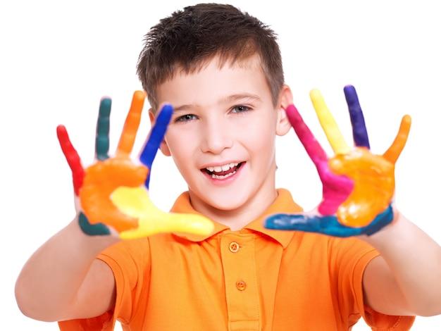 Gelukkig lachend jongen met een geschilderde handen op wit wordt geïsoleerd.