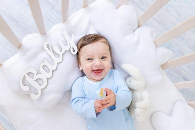 Gelukkig lachend jongetje in de wieg met de inscriptie baby in een blauwe bodysuit, schattige vrolijke kleine baby in de slaapkamer