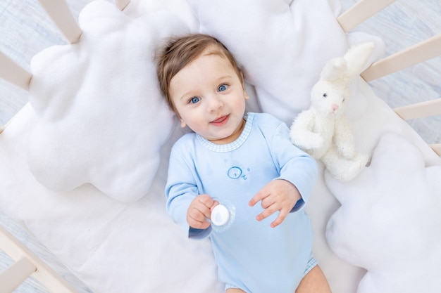 Gelukkig lachend jongetje in wieg in blauwe romper, schattige vrolijke kleine baby in slaapkamer