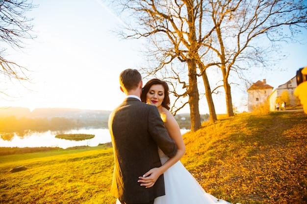 Gelukkig lachend jonggehuwden buiten lopen, zoenen en omhelzen op hun trouwdag