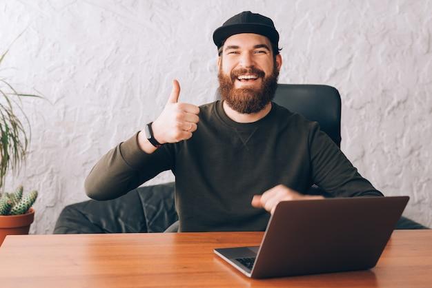 Gelukkig lachend kantoor werknemer man zittend op zijn tafel en duimen opdagen gebaar