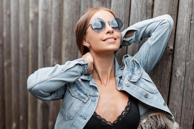 Gelukkig lachend kaukasisch meisje met vintage ronde blauwe zonnebril in fashion jeans kleding met kanten lingerie poseren in de buurt van houten muur