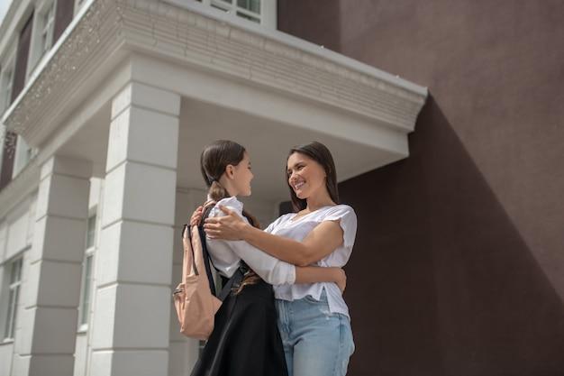 Gelukkig lachend kijken elkaar moeder met schoolmeisje permanent in de buurt van school