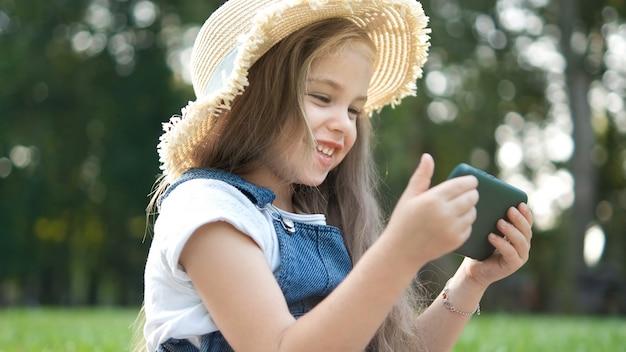 Gelukkig lachend kind meisje op zoek in mobiele telefoon buiten in de zomer.