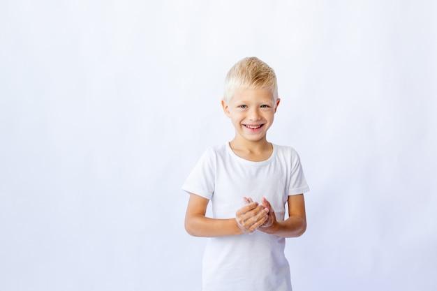 Gelukkig lachend klein kind dragen witte t-shirt zijn handen wassen in de badkamer met spiegel