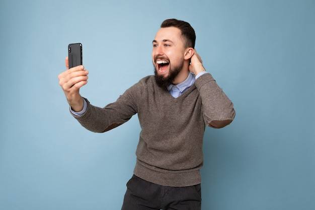 Gelukkig lachend knappe jonge man met casual stijlvolle kleding staande geïsoleerd over achtergrond muur met smartphone selfie foto kijken naar mobiele telefoon schermweergave.