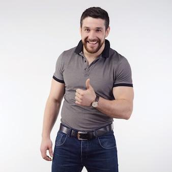 Gelukkig lachend knipogende jonge man met duimen omhoog