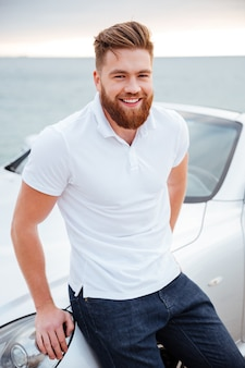 Gelukkig lachend kralen man zittend op zijn auto geparkeerd op het strand