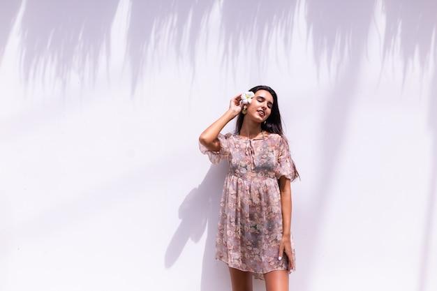 Gelukkig lachend langharige vrouw in jurk staat op witte muur