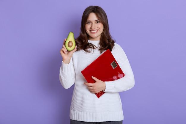 Gelukkig lachend mager wijfje dat witte sweater draagt die vloerschalen en de helft van avocado in handen houdt