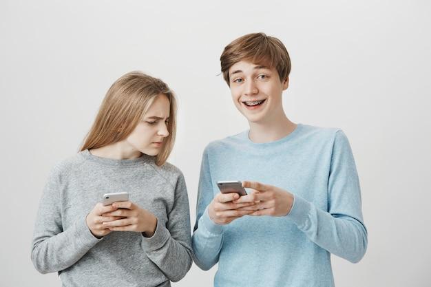 Gelukkig lachend man met bretels lachen om grappige bericht, meisje gluren zijn mobiele telefoon-scherm