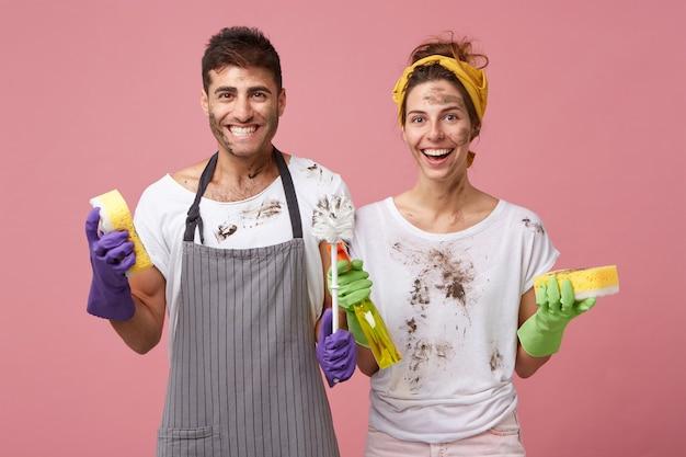 Gelukkig lachend mannetje en vrouw die vrijetijdskleding dragen die gelukkig zijn om de voorjaarsschoonmaak te beëindigen