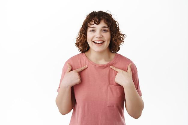 Gelukkig lachend meisje dat naar zichzelf wijst en glimlacht terwijl ze in een t-shirt op wit staat