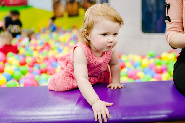 Gelukkig lachend meisje dat speelt met speelgoed, kleurrijke ballen in de speeltuin, ballenbak in de speelkamer. klein schattig kind met plezier in ballenbak op verjaardagsfeestje in pretpark voor kinderen.