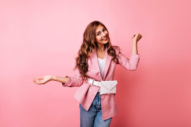 Gelukkig lachend meisje goede emoties uitdrukken op pastel. aantrekkelijk vrouwelijk model in jeans en roze jasje lachen.