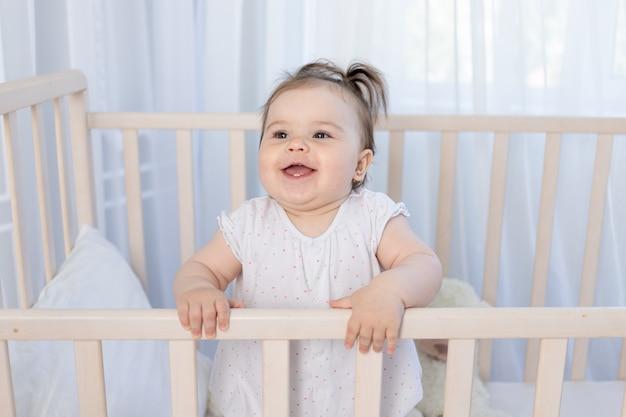 Gelukkig lachend meisje in de wieg in de kinderkamer in een wit rompertje