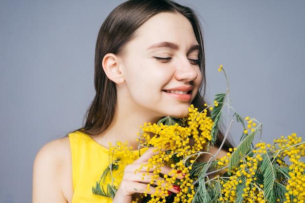 Gelukkig lachend meisje in een gele jurk die een geurige gele mimosa ruikt
