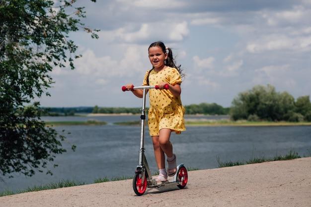 Gelukkig lachend meisje in een gele jurk die op een scooter rijdt, het meisje heeft een goede tijd en geniet van een gezin met...