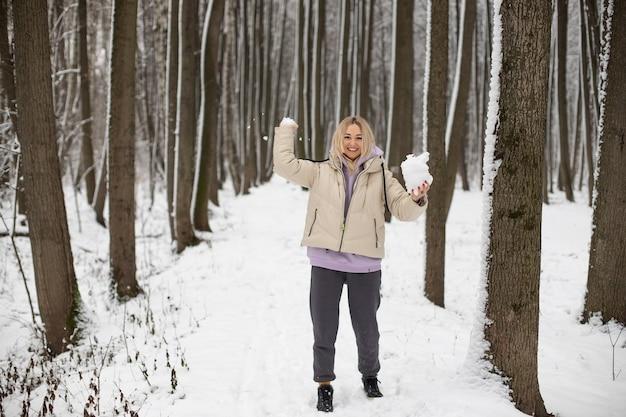 Gelukkig lachend meisje in het park in de winter speelt sneeuwballen. gooit sneeuw naar de camera