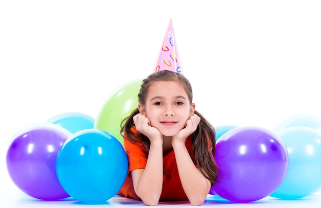 Gelukkig lachend meisje in oranje t-shirt liggend op de vloer met kleurrijke ballonnen - geïsoleerd op een witte.