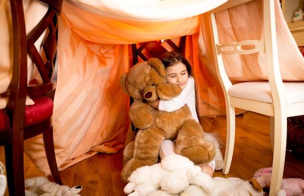 Gelukkig lachend meisje in pyjama knuffelen teddybeer bij zelfgemaakte huis