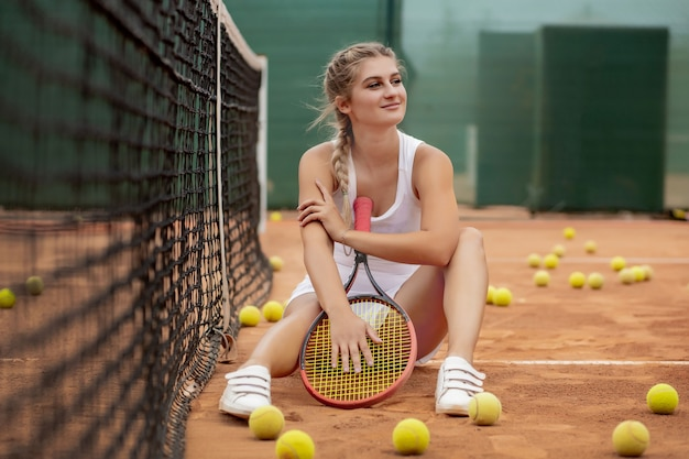 Gelukkig lachend meisje is aan het koelen in de buurt van tennisnet op de tennisbaan met racket in handen.