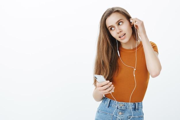 Gelukkig lachend meisje koptelefoon op, luister podcast of muziek op mobiele telefoon