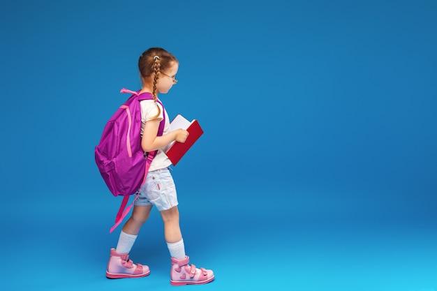Gelukkig lachend meisje met bril en een boek gaat naar school