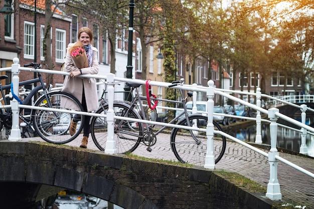 Gelukkig lachend meisje met een boeket tulpen op een straat in amsterdam