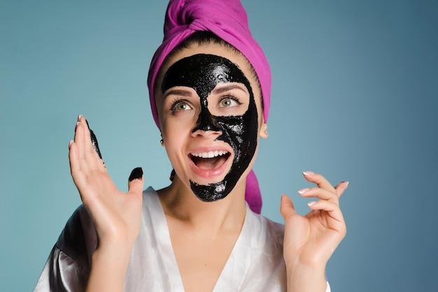 Gelukkig lachend meisje met een roze handdoek n agolovo zet een zwart masker tegen acne op het gezicht