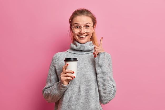 Gelukkig lachend meisje met positieve uitdrukkingspunten hierboven, houdt warme drank in kartonnen beker, gekleed in losse grijze trui
