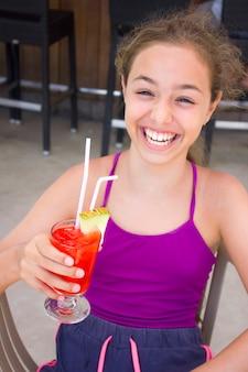 Gelukkig lachend meisje met rode cocktail in haar hand
