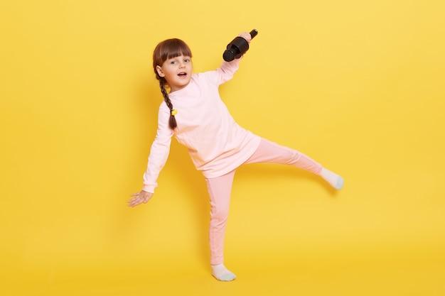 Gelukkig lachend meisje springen en zingen in de microfoon, kleine zanger dragen casual kleding poseren geïsoleerd op gele achtergrond, kind met pigtails presteren.