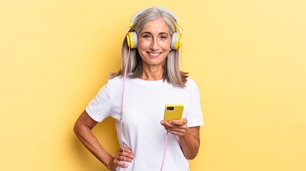 Gelukkig lachend met een hand op de heup en zelfverzekerde, positieve, trotse en vriendelijke houding met een koptelefoon