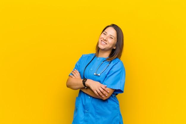 Gelukkig lachend met gekruiste armen, met een ontspannen, positieve en tevreden pose geïsoleerd tegen gele muur