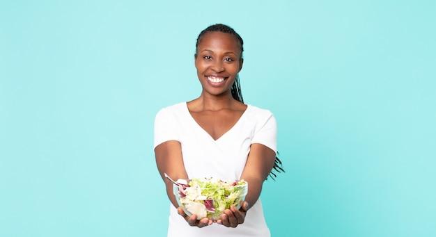 Gelukkig lachend met vriendelijk en aanbiedend en tonend een concept en een salade vasthoudend?