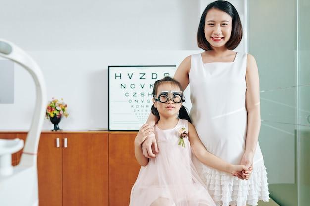 Gelukkig lachend moeder en haar dochtertje in testglazen in kantoor van optometrist