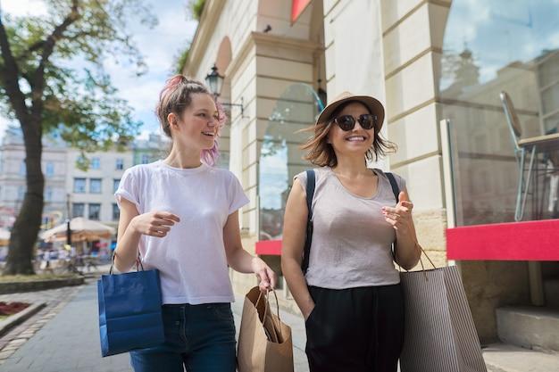 Gelukkig lachend moeder en tienerdochter wandelen samen met boodschappentassen.