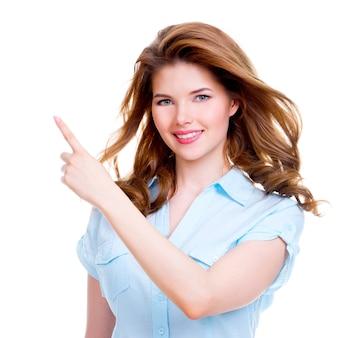 Gelukkig lachend mooie jonge vrouw toont een vinger in de zijkant - geïsoleerd op wit.