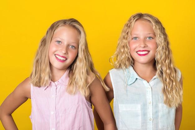 Gelukkig lachend mooie tiener tweeling meisjes lachen met een perfecte glimlach. mensen, emoties, tieners en vriendschapsconcept. schattige zussen met blond haar en geweldige ogen op gele muur.
