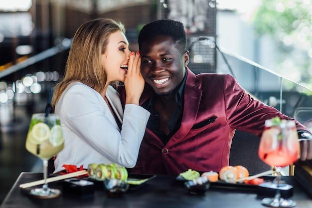 Gelukkig lachend paar jonge volwassen elkaar voeden met sushi in restaurant.