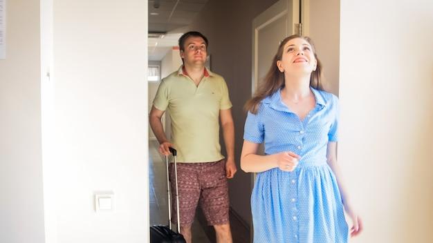 Gelukkig lachend paar verliefd dat hotelkamer binnenkomt op hun zomervakantie.
